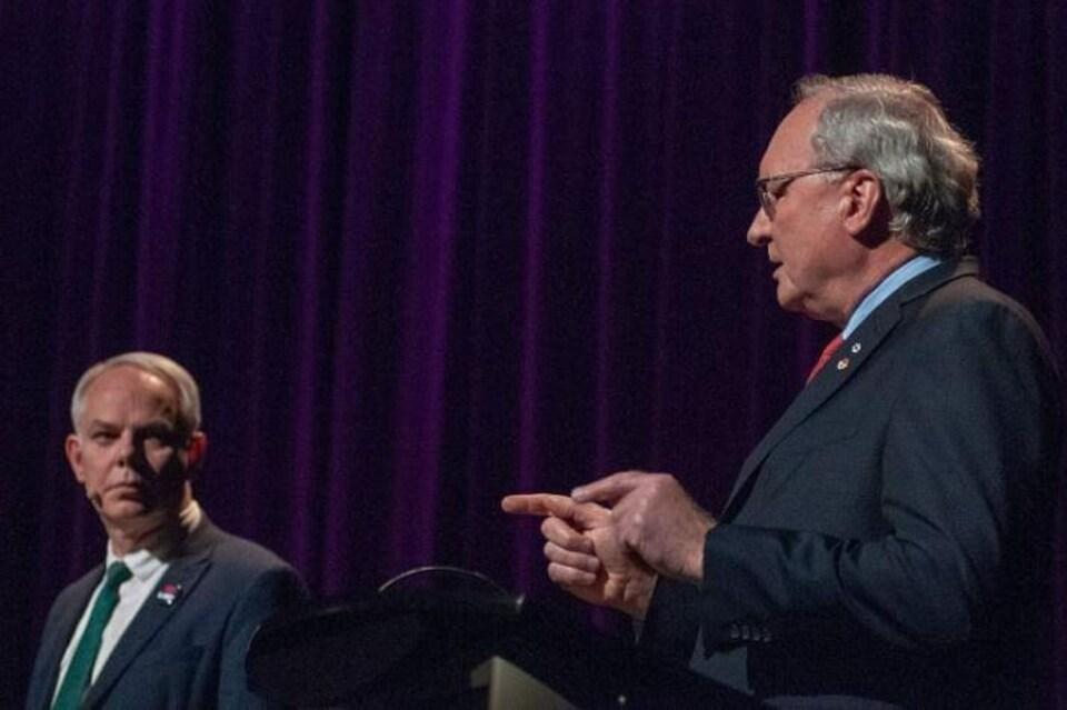 Deux hommes vus de profil, debout sur une scène, débattent devant un rideau.