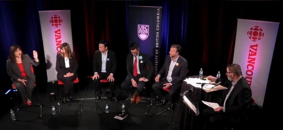 Les candidats Wai Young, Shauna Sylvester, Ken Sim, Hector Bremner, Kennedy Stewart et le modérateur Stephen Quinn sur scène, en plein débat.