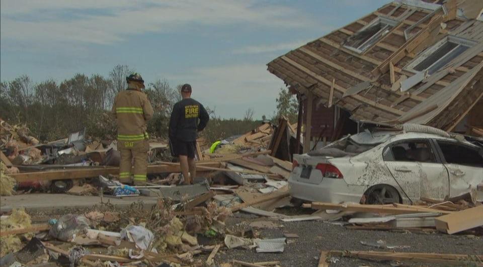 Des pompiers se tiennent sur un tas de débris là où se tenait une maison.