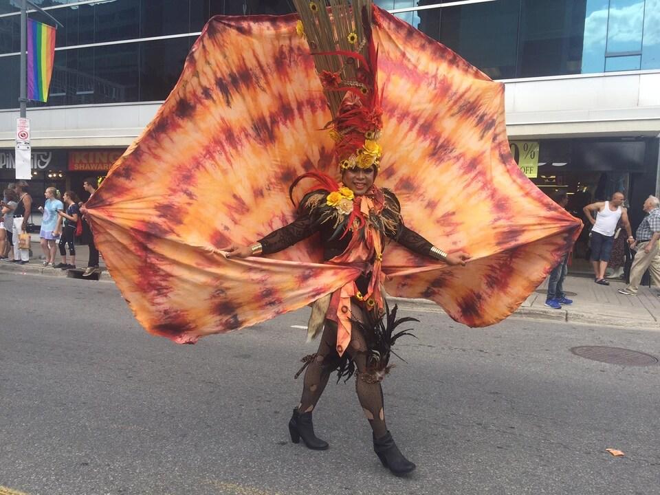 Un participant a un costume orangé et des plumes noires.