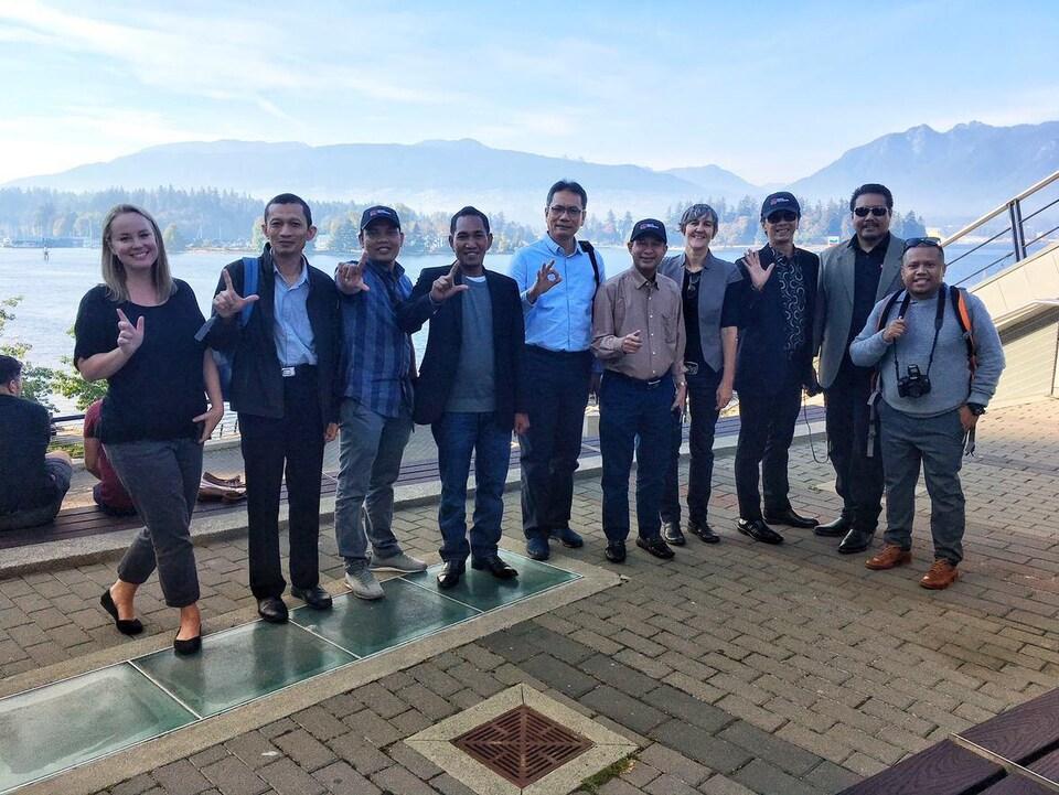 Un groupe de dix personnes pose avec des montagnes en arrière-plan.