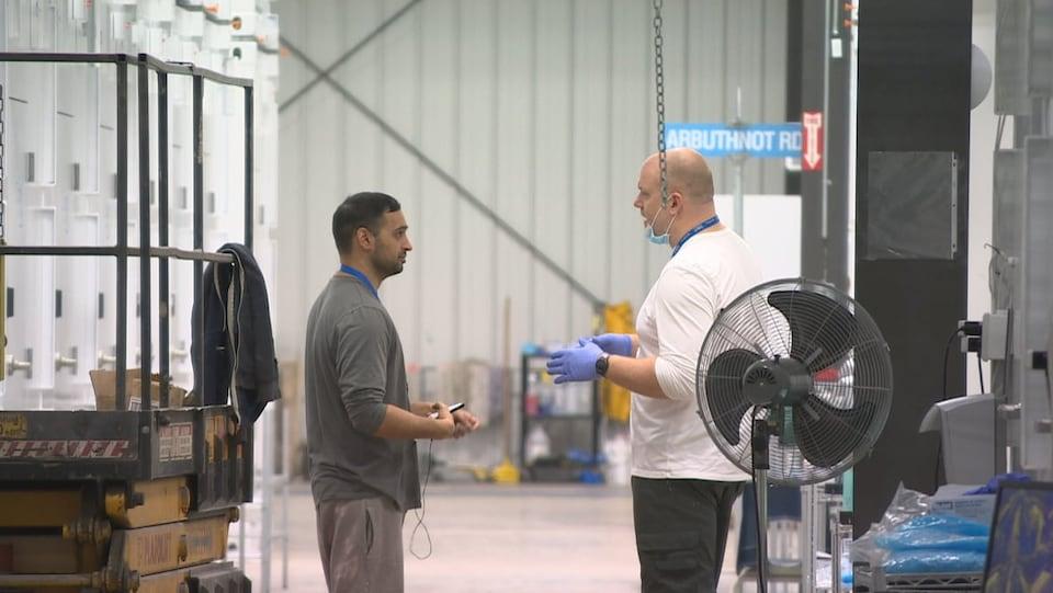 Deux hommes parlent dans une usine.