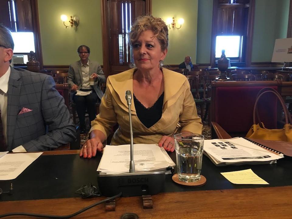 Katherine d'Entremont assise à une table s'apprête à lire son rapport à l'Assemblée législative