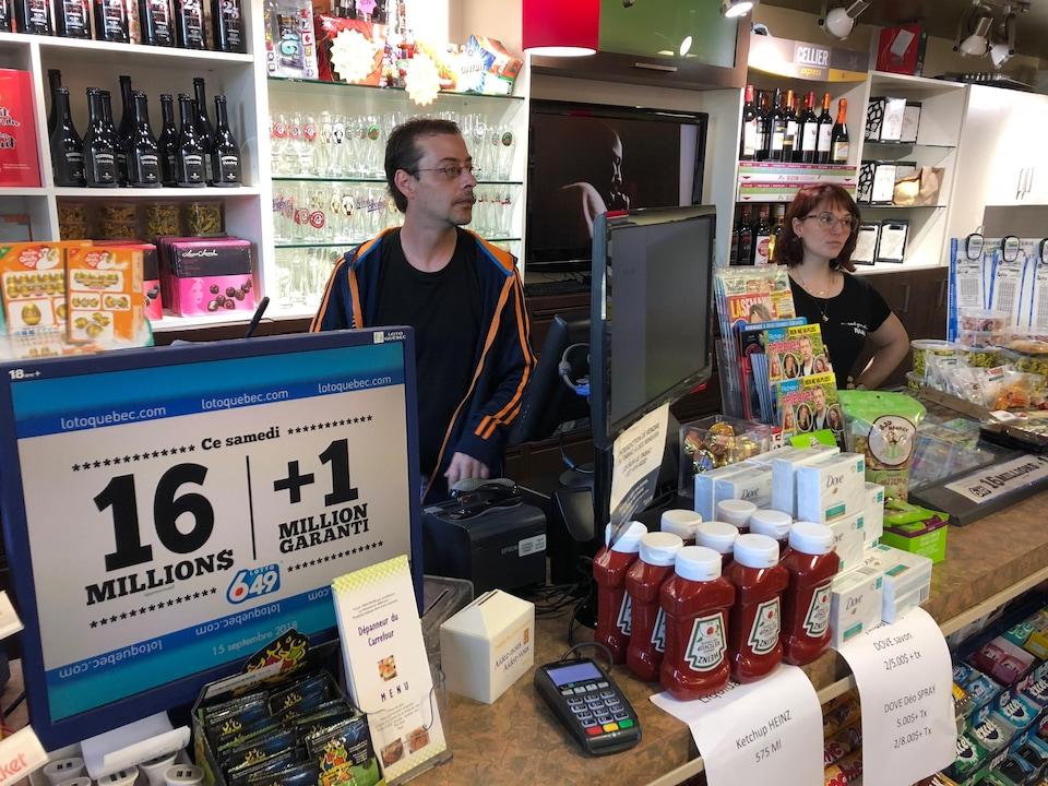 Un homme et une femme derrière le comptoir d'un dépanneur. Derrière eux, des bouteilles d'alcool et des verres sur des tablettes.