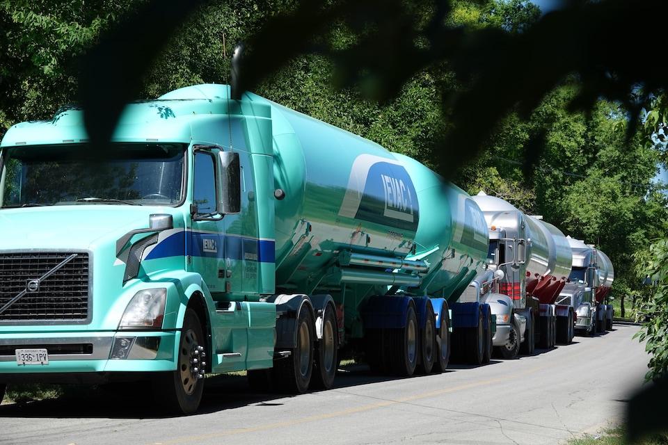 Trois camions citernes faisant la queue sur une route.