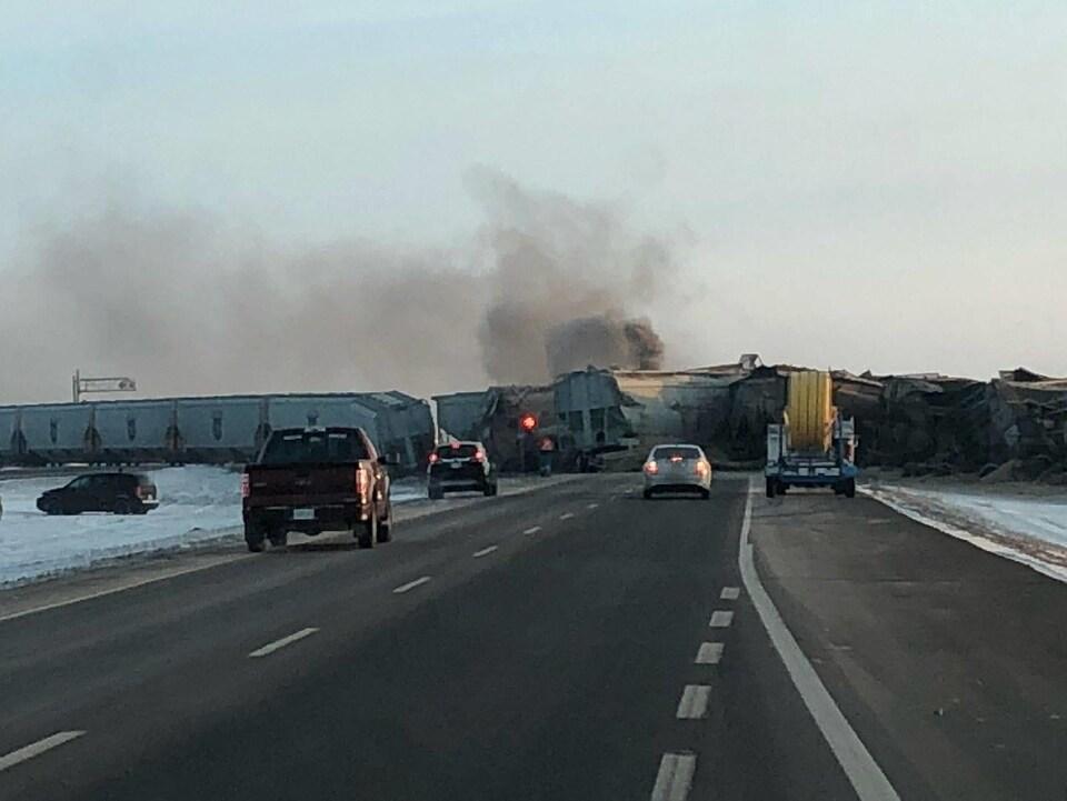 Les wagons du train barrent la route 11 à plusieurs voitures, de la fumée s'échappe de ces wagons cabossés.