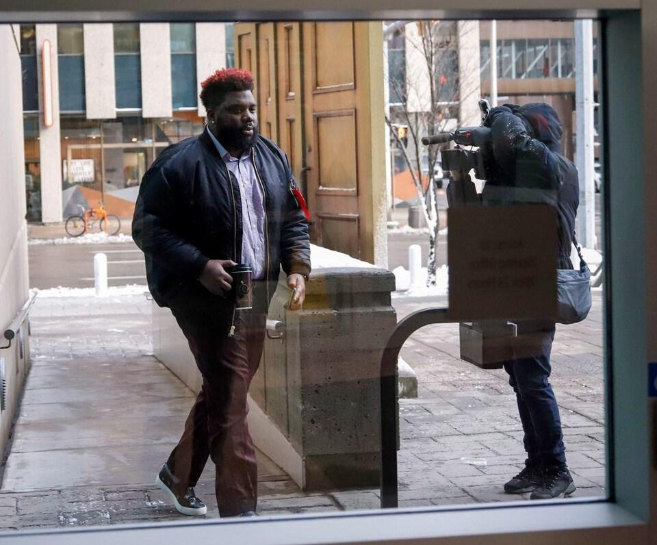 Derek Dennis arrive au palais de justice, café à la main.