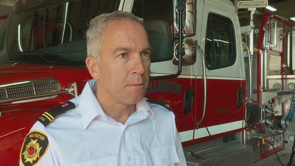 Desmond Arsenault en entrevue devant un camion de pompiers.