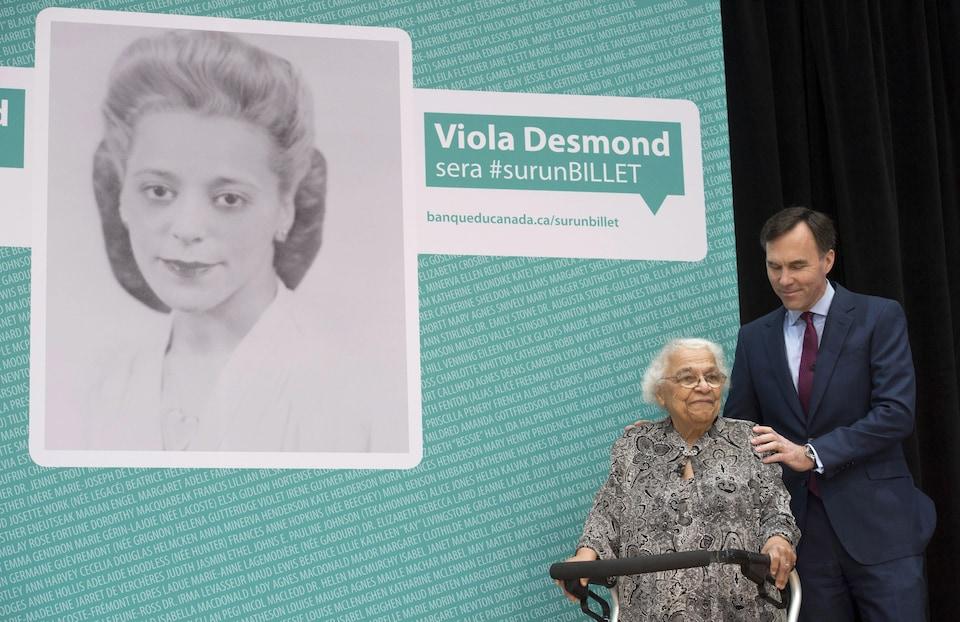 Le ministre des Finances, Bill Morneau, pose une main sur l'épaule de Wanda Robson, soeur de Viola Desmond, devant une affiche annonçant que Desmond a été choisie pour figurer sur les billets de 10 $.