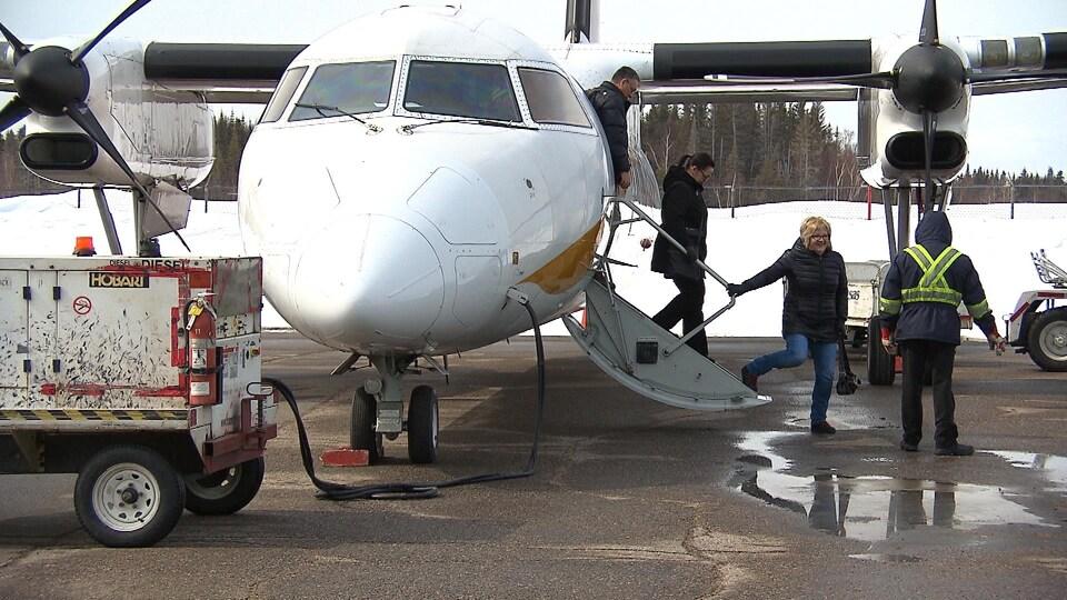 Trois personnes descendent les escaliers qui mènent sur la piste d'atterrissage.
