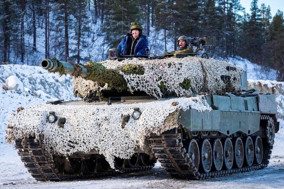 La première ministre dans un char avec un soldat.