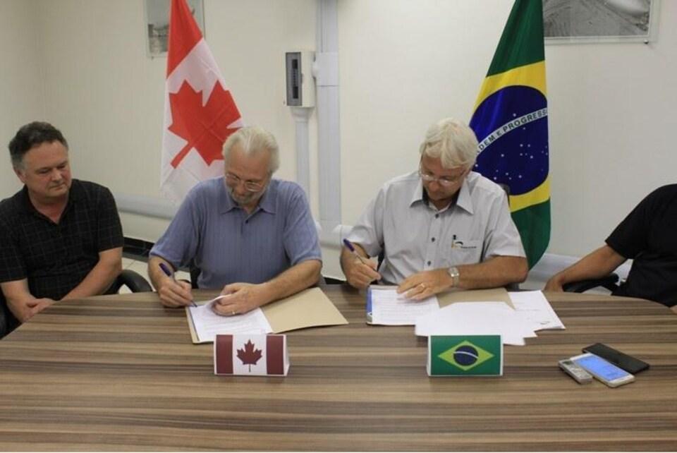 Deux hommes signent chacun leur copie d'un contrat. Ils sont assis à une table. Devant eux il y a un petit petit drapeau de leur pays respectif, le Canada et le Brésil. Un troisième homme les regarde.