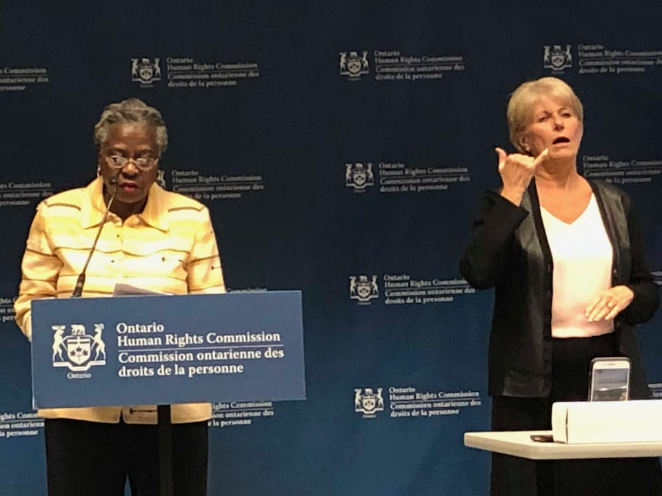 On voit Valarie Steele du Comité d'action et de défense des Noirs en train de prendre la parole à la conférence de presse de la Commission ontarienne des droits de la personne.