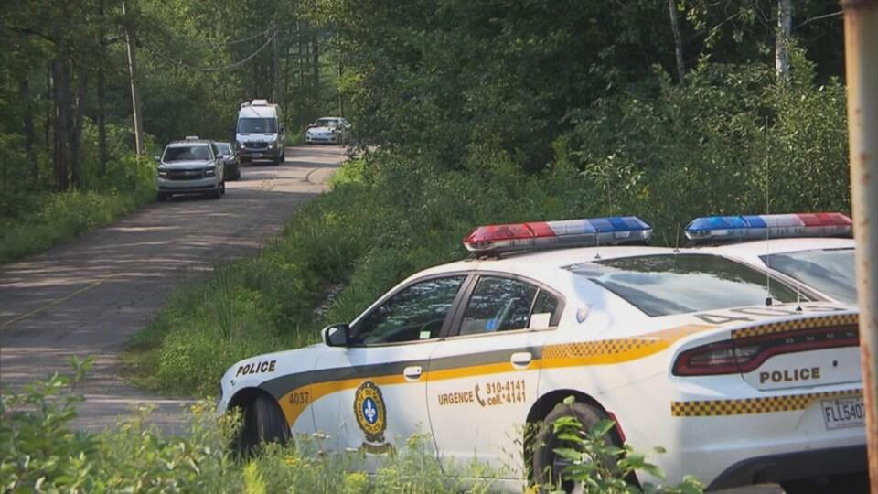 Des autopatrouilles de la Sûreté du Québec stationnés sur une route de campagne.