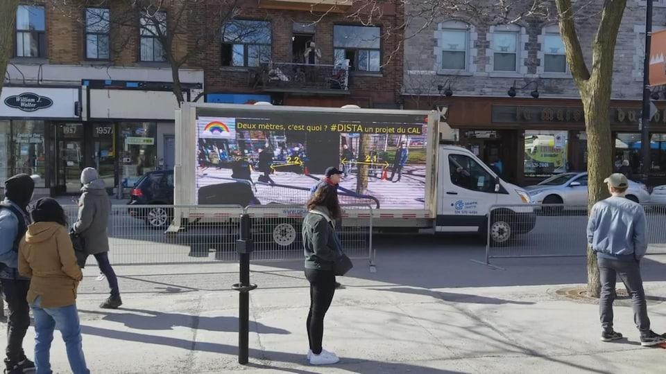 Un camion devant un commerce qui montre aux gens en file sur le trottoir la distance qu'ils maintiennent entre eux.