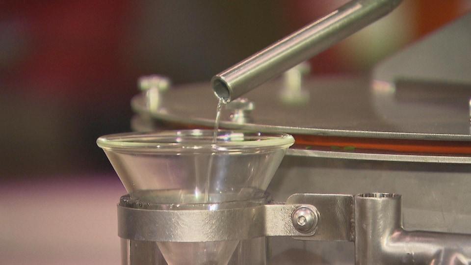 Un liquide sort d'une tige et se verse dans une contenant