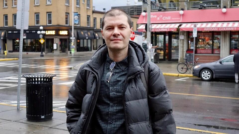 Un homme photographié dans une rue passante par une journée pluvieuse