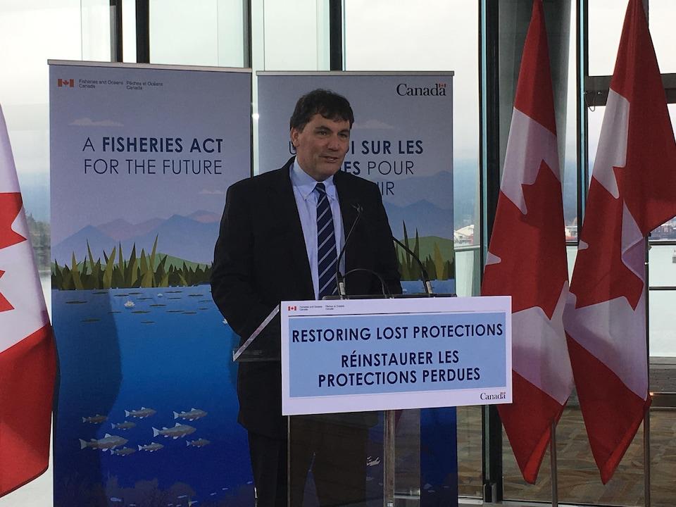 Un homme parle au micro en conférence de presse avec des affiches sur lesquelles il est inscrit: réinstaurer les protections perdues.