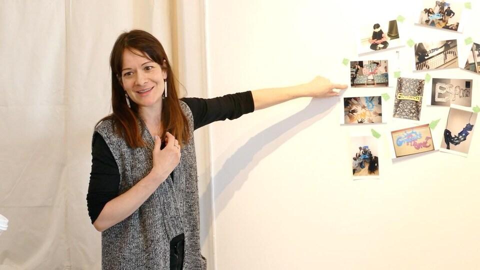 L'artiste Dominique Rey pointe au collage de photos sur le mur.