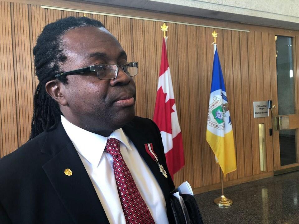Un homme en costume et cravate rouge devant un drapeau du Canada et un drapeau de la Ville de Winnipeg.