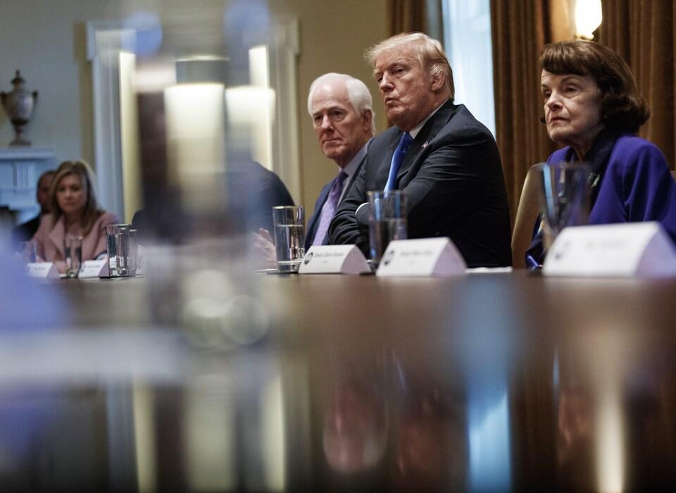 Donald Trump entouré de la représentante du Tennessee Dianne Feinstein (gauche), du sénateur du Texas John Cornyn et de la sénatrice de la Californie Marsha Blackburn (droite).