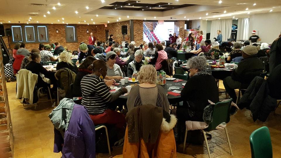 Plan d'ensemble de la salle, les invitées étant assises autour d'une quinzaine de tables rondes.