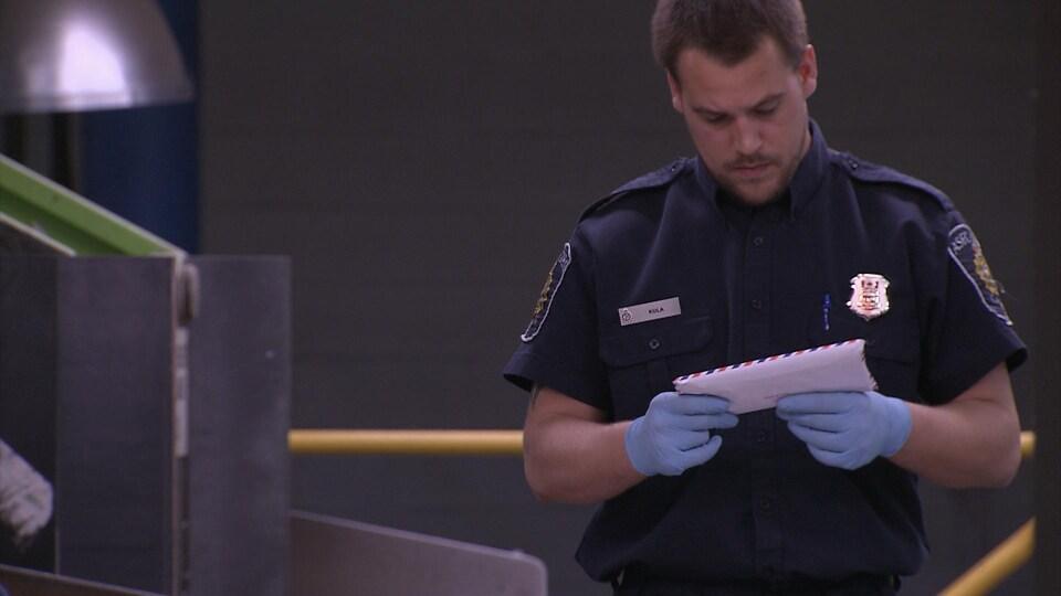 Un agent des services douaniers examine une lettre.