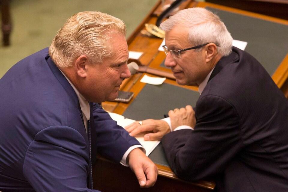 Photo de deux hommes en complet qui sont penchés l'un vers l'autre pour se parler dans l'oreille.