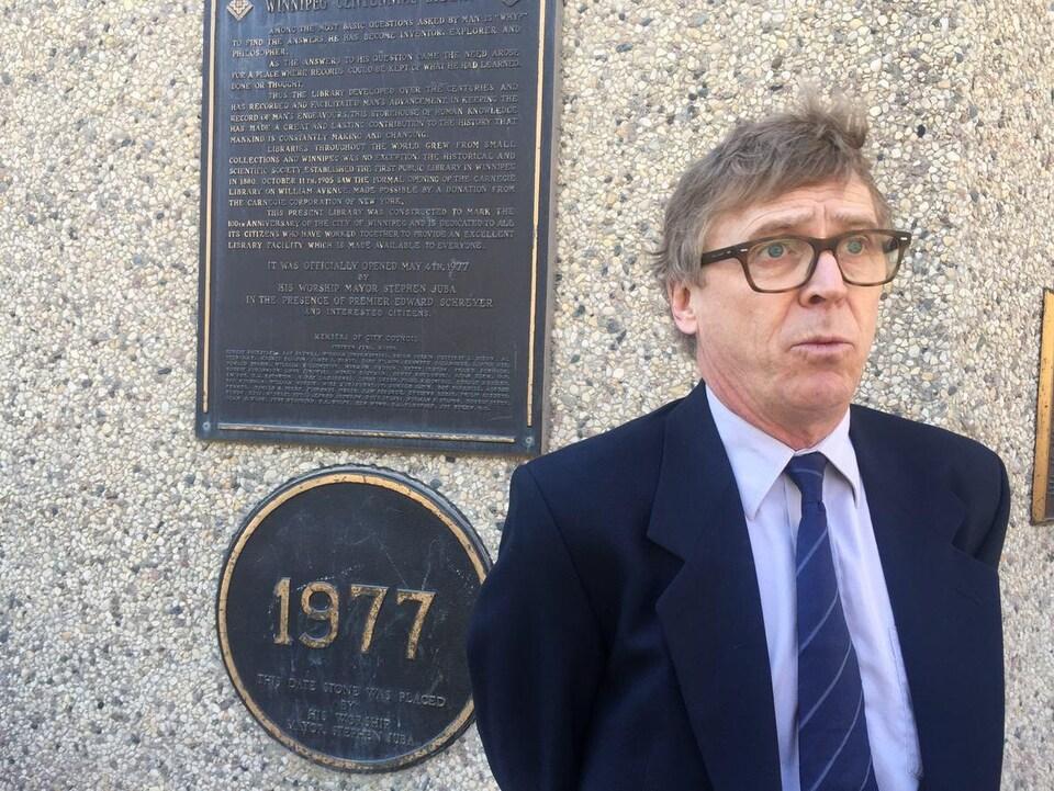 Un homme à lunettes, en costume et cravate bleu devant un bâtiment de 1977.