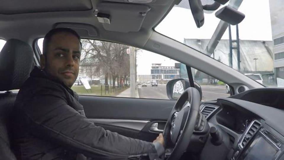 Le Dr Naheed Dosani à bord de sa voiture dans laquelle il se déplace pour visiter ses patients.