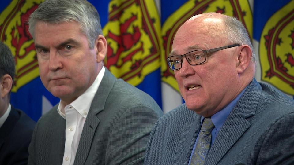 Stephen McNeil et Robert Strang devant des drapeaux de la Nouvelle-Écosse.