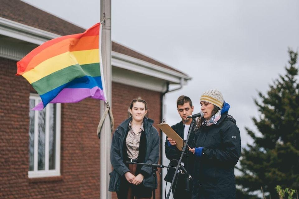 Une personne parle au micro et deux autres se tiennent à ses côtés alors que le drapeau arc-en-ciel est hissé sur un mât.