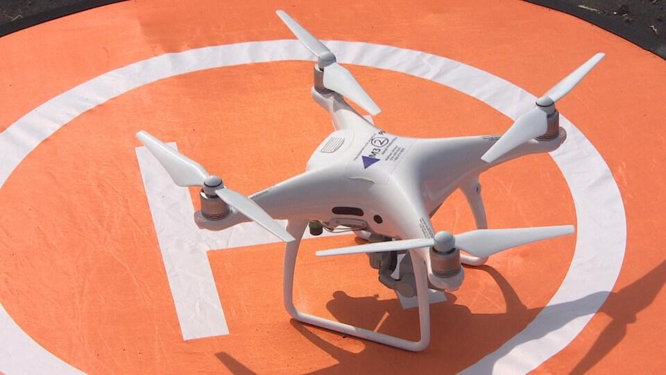 Gros plan sur un drone blanc, positionné sur une petite plateforme orange sur le sol.