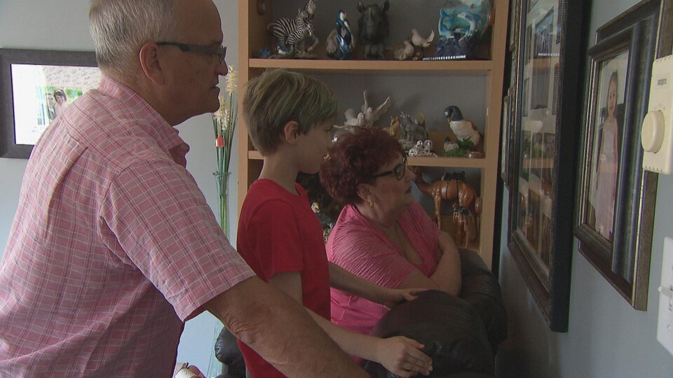 Dylan et ses grands-parents, Roseline et Jean-Claude Robichaud, regardent des photos de famille.