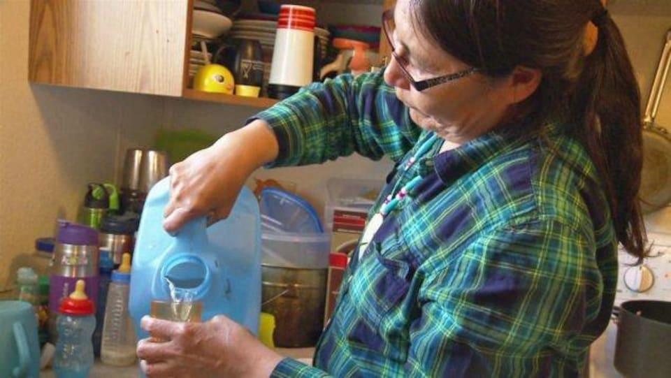 Une femme remplit un verre d'eau.