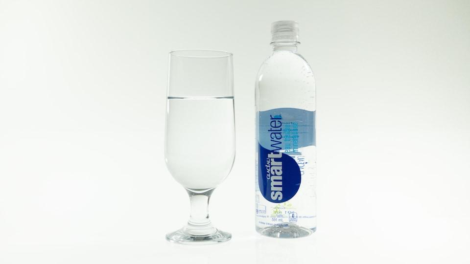 Une bouteille d'eau de marque Smartwater et un verre d'eau.