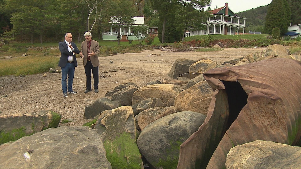 Le maire et un journaliste regardent au loin un vieux tuyaux près de deux maisons.
