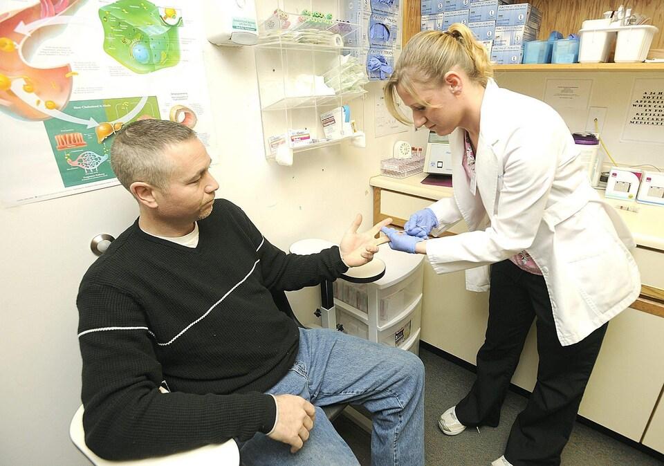 Une infirmière prélève un échantillon de sang.