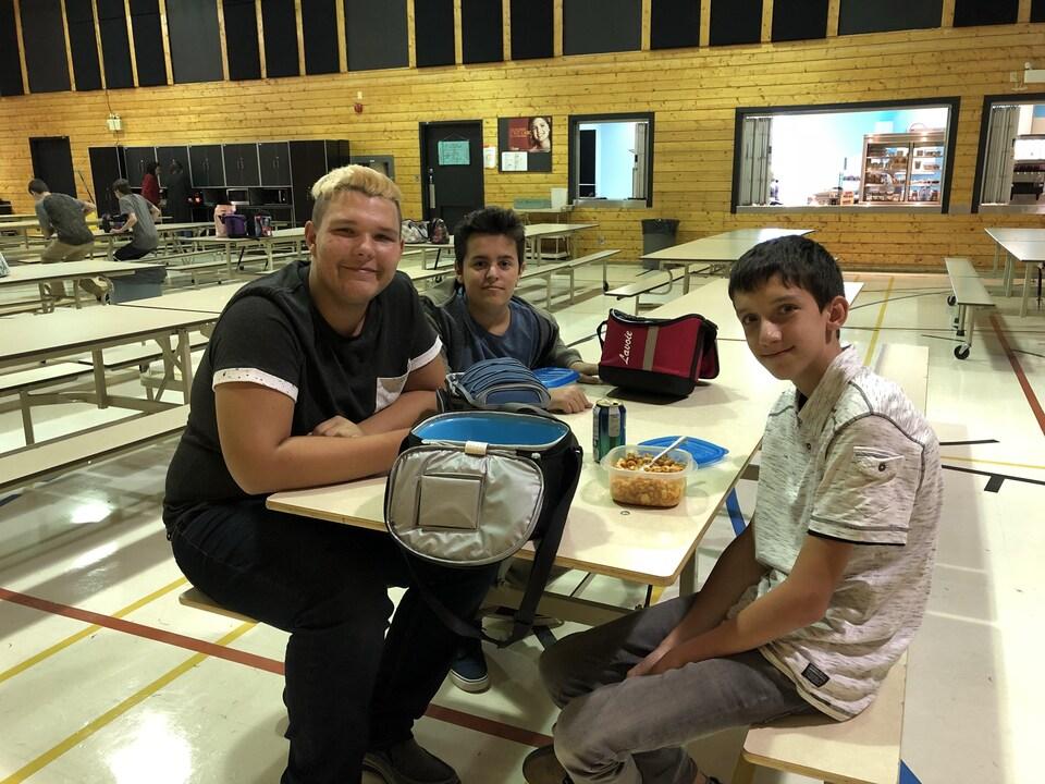Dylan, Alex et Olivier assis à une table dans la cafétéria.