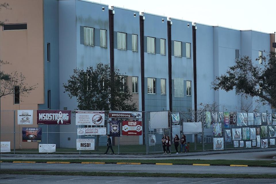 Un bâtiment est entouré d'une clôture sur laquelle sont posées des affiches à la mémoire des victimes de la tuerie.