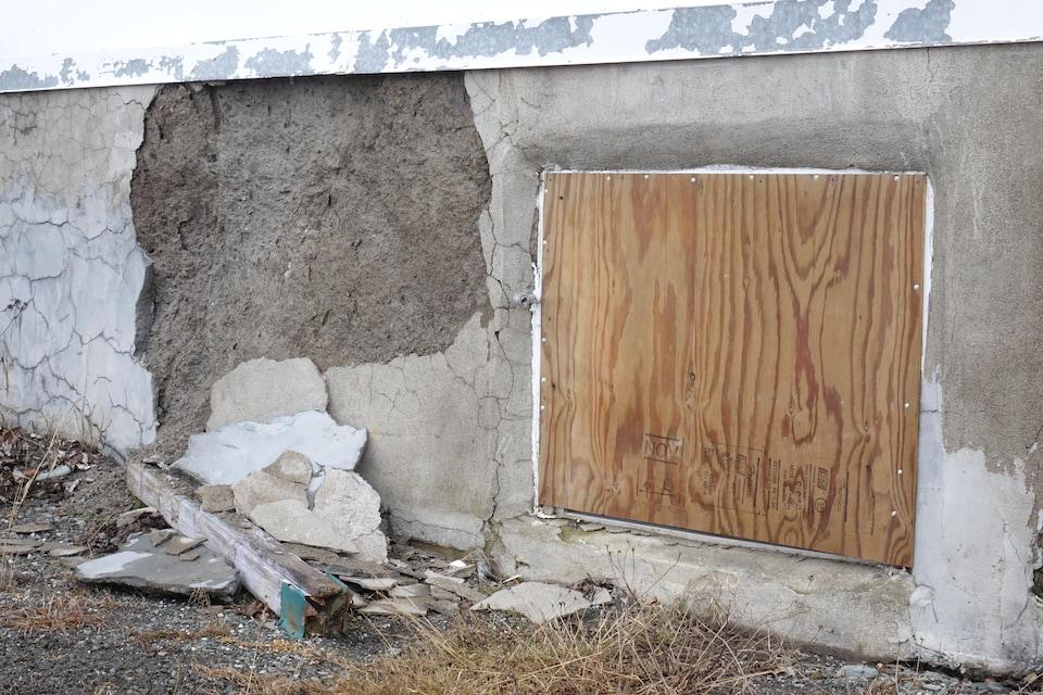 Planche de bois dans une fenêtre et crépi du solage en morceaux