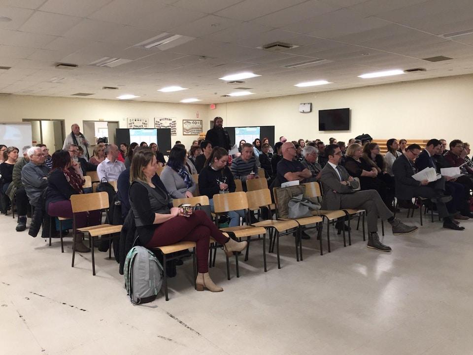 Une centaine de personnes sont assises dans une grande salle et regarde une présentation.