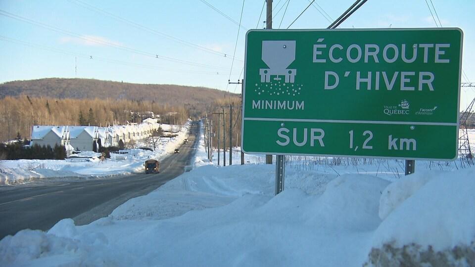 On voit un panneau au bord d'une route de campagne. On peut y lire «écoroute d'hiver sur 1,2 km».