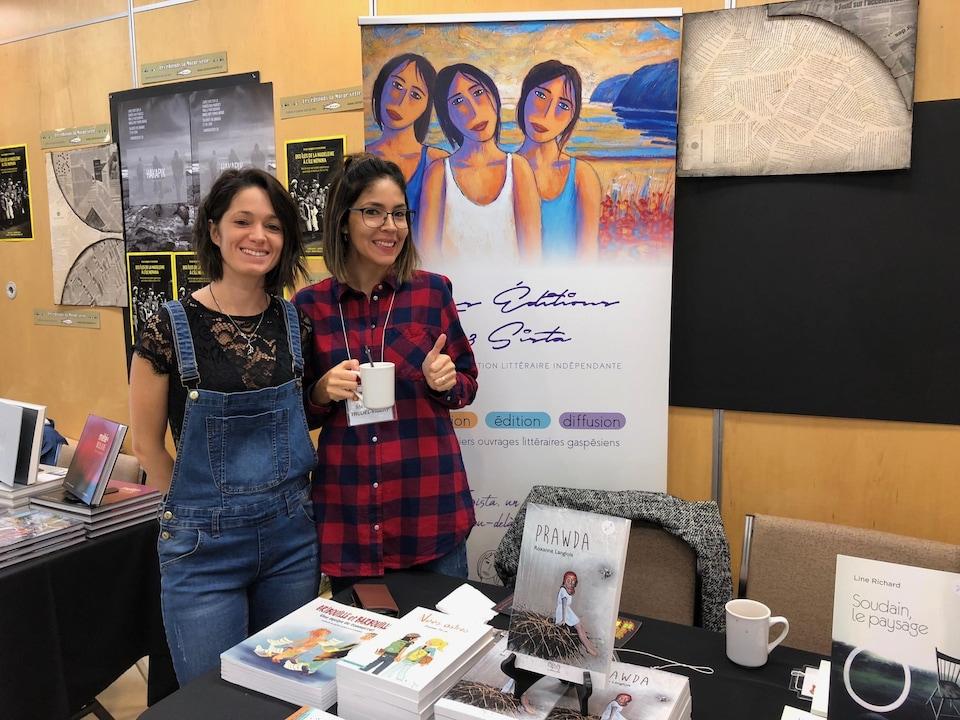 Les deux femmes sourient devant leur kiosque où sont présentés les livres de leur maison d'édition.