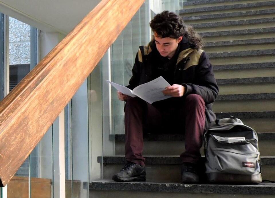 On voit Edwin Cotar en train de lire un document, assis dans un escalier.