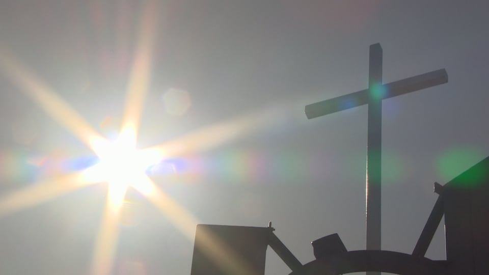Les rayons du soleil et une croix sur une église.