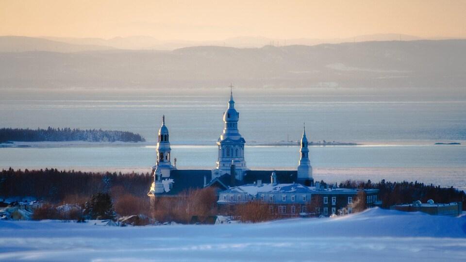 Point de vue sur une église qui se situe devant le fleuve Saint-Laurent, à Trois-Pistoles. On remarque les montagnes au loin qui trace une ligne d'horizon en hiver.
