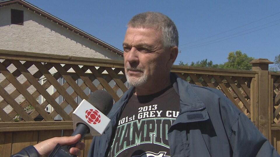 M. Robinson écoute attentivement la journaliste poser sa question. Il porte un chandail noir de l'équipe de football saskatchewanaise, les Roughriders.