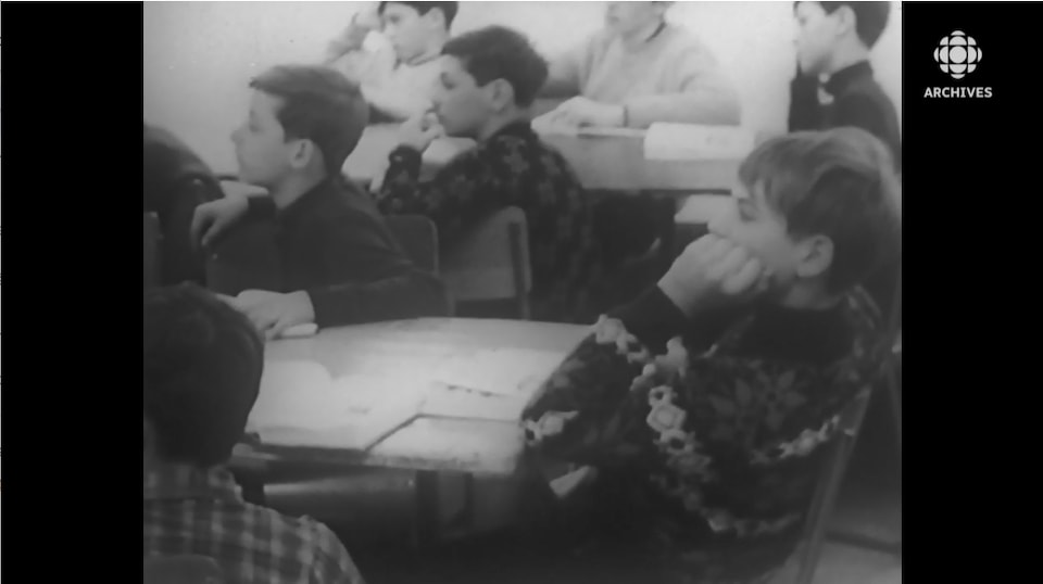 De jeunes garçons en chandails de laine, à l'écoute d'une classe.