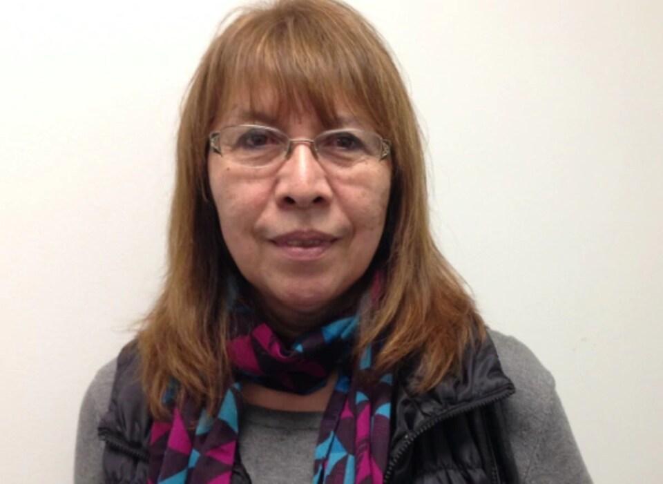 Une dame qui porte des lunettes et une écharpe